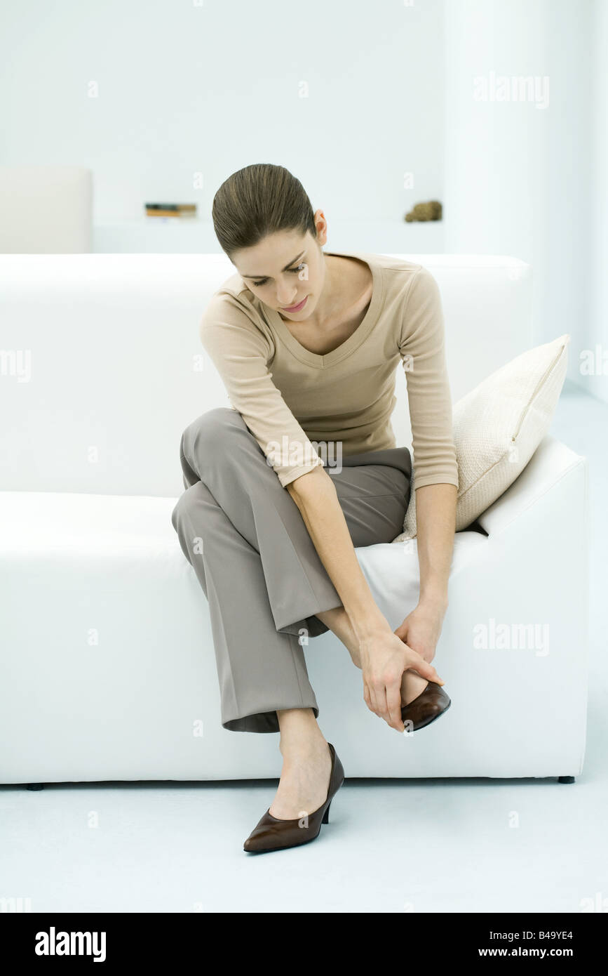 Woman sitting on sofa, putting on shoe, full length - Stock Image