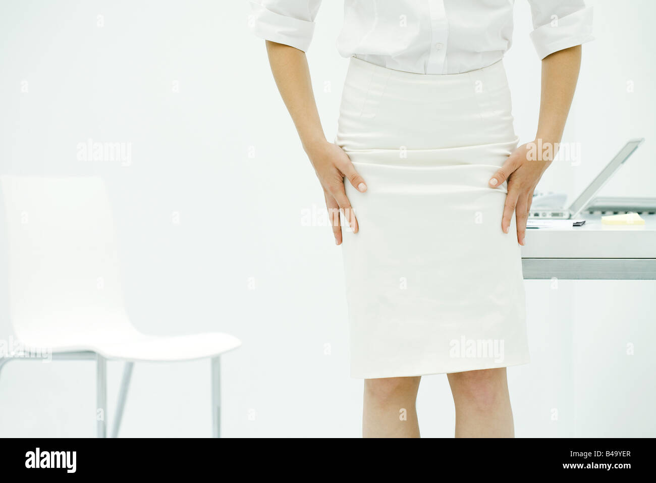 Professional woman in office, adjusting wrinkled skirt, cropped view - Stock Image