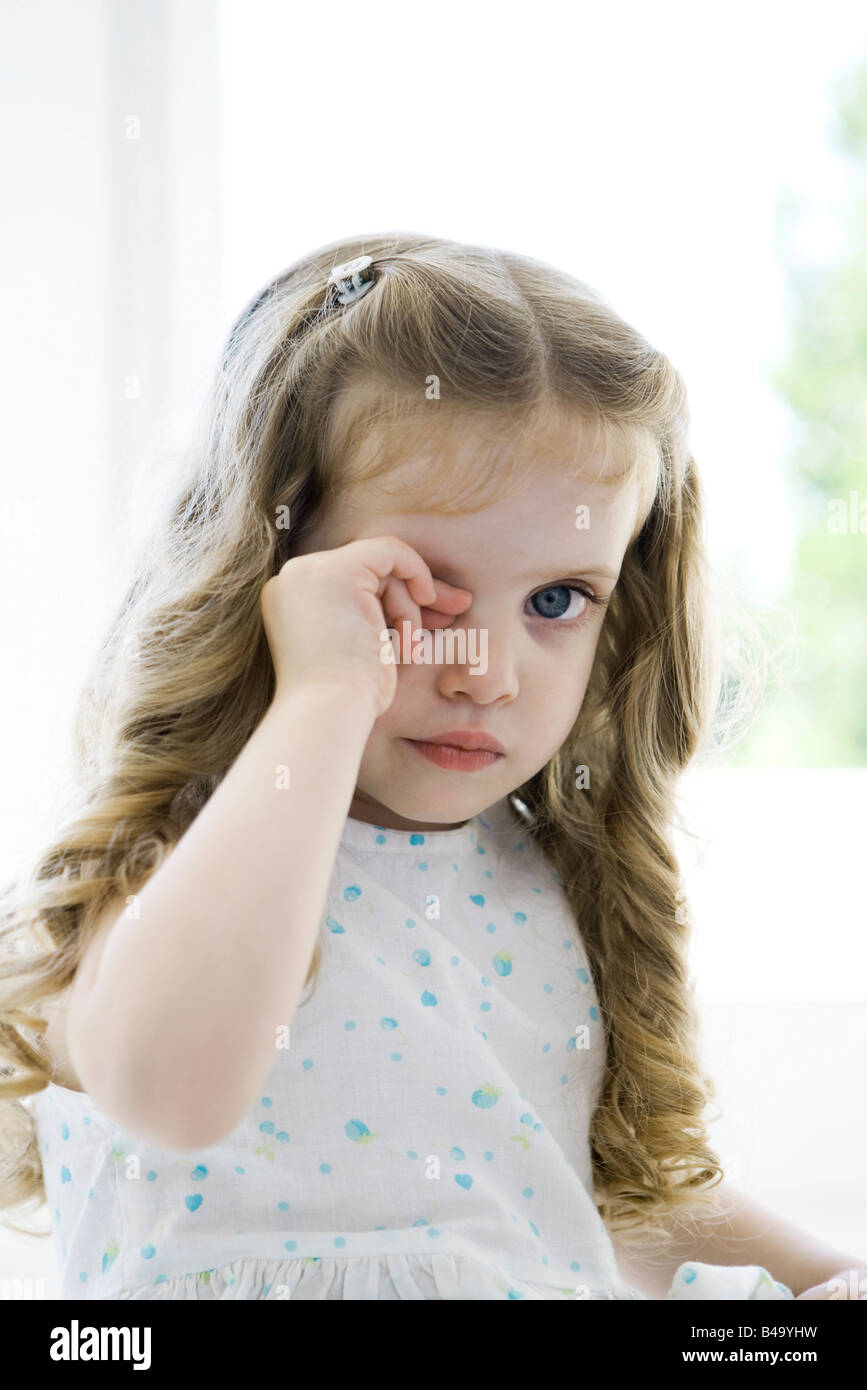 Little girl rubbing her eye, looking at camera - Stock Image