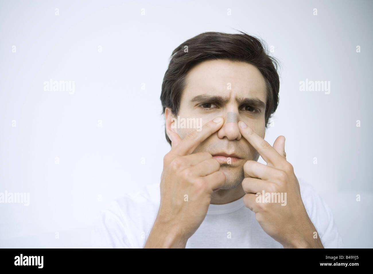 Man applying adhesive bandage on his nose, looking at camera Stock Photo