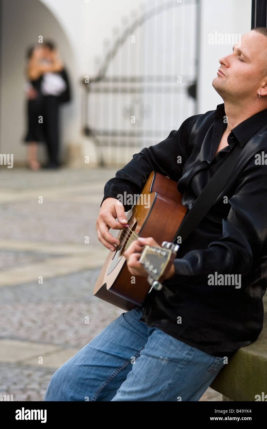 A street musician playing his guitar serenades a romantic couple kissing out of focus in the background - Stock Image