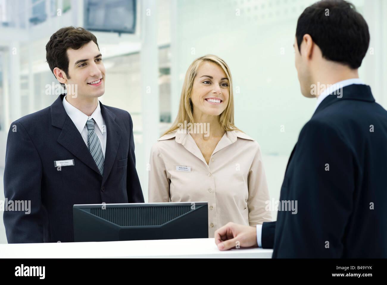 Customer service representatives smiling at businessman waiting at counter Stock Photo