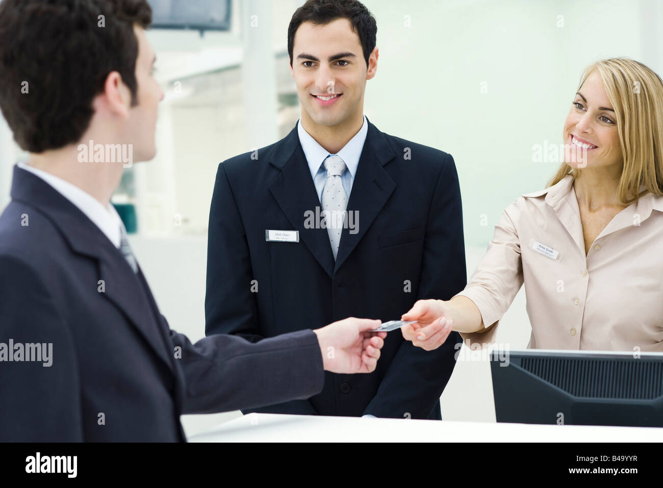 Man giving credit card to smiling customer service representatives Stock Photo