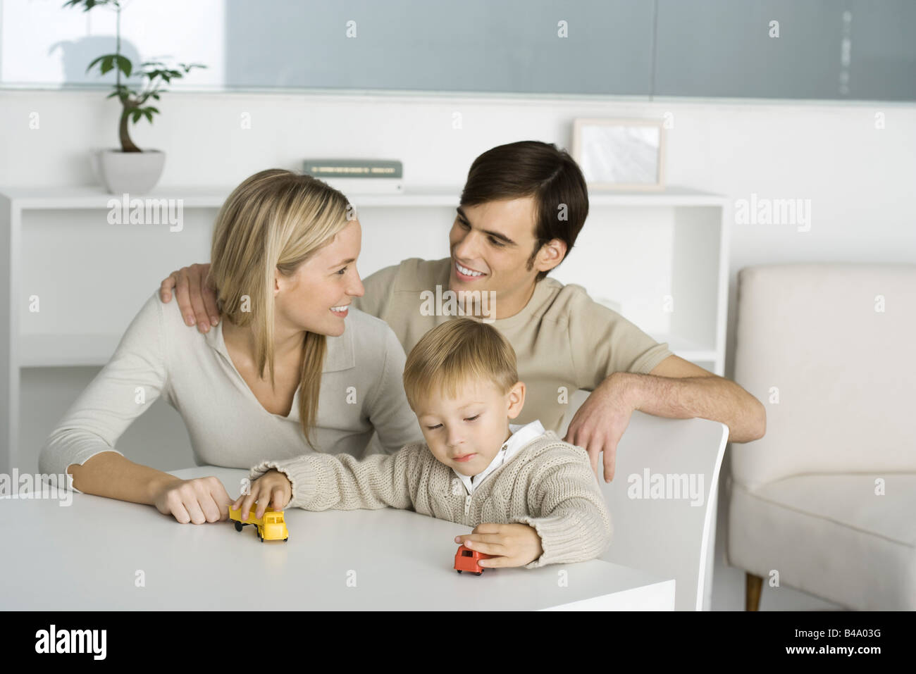 Family at table, boy playing with toy trucks, parents smiling at each other - Stock Image