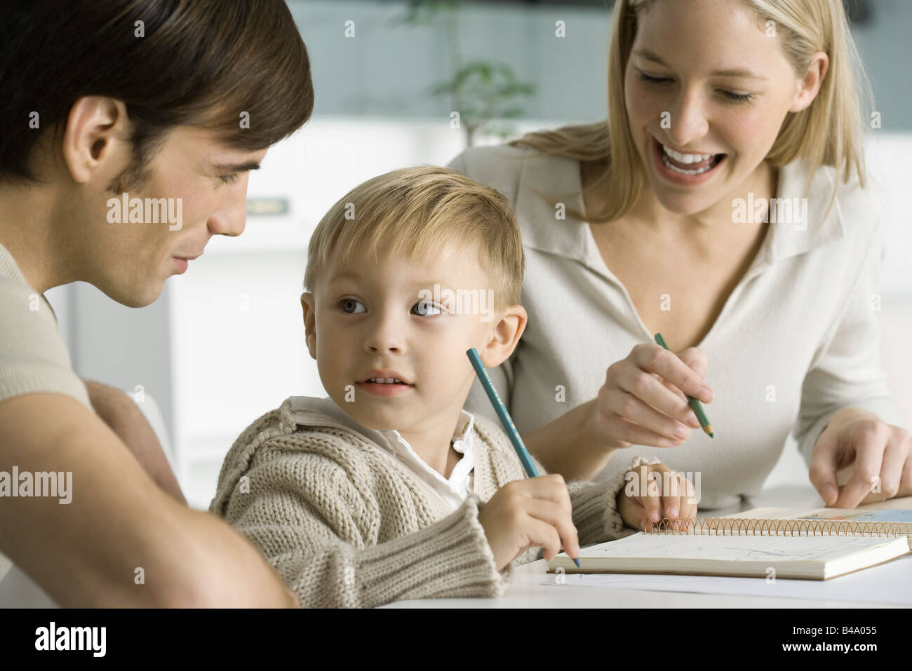 Little boy coloring at table with parents, looking at father - Stock Image