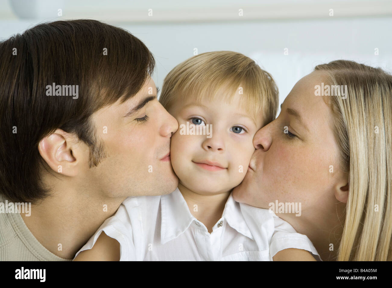 Parents kissing little boy's cheeks, boy smiling at camera Stock Photo