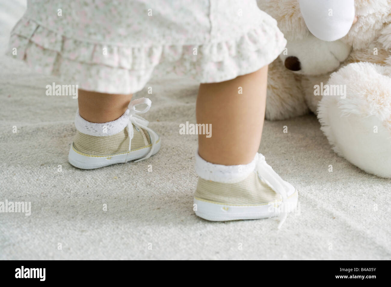 Toddler girl bending over stuffed toy, cropped view - Stock Image
