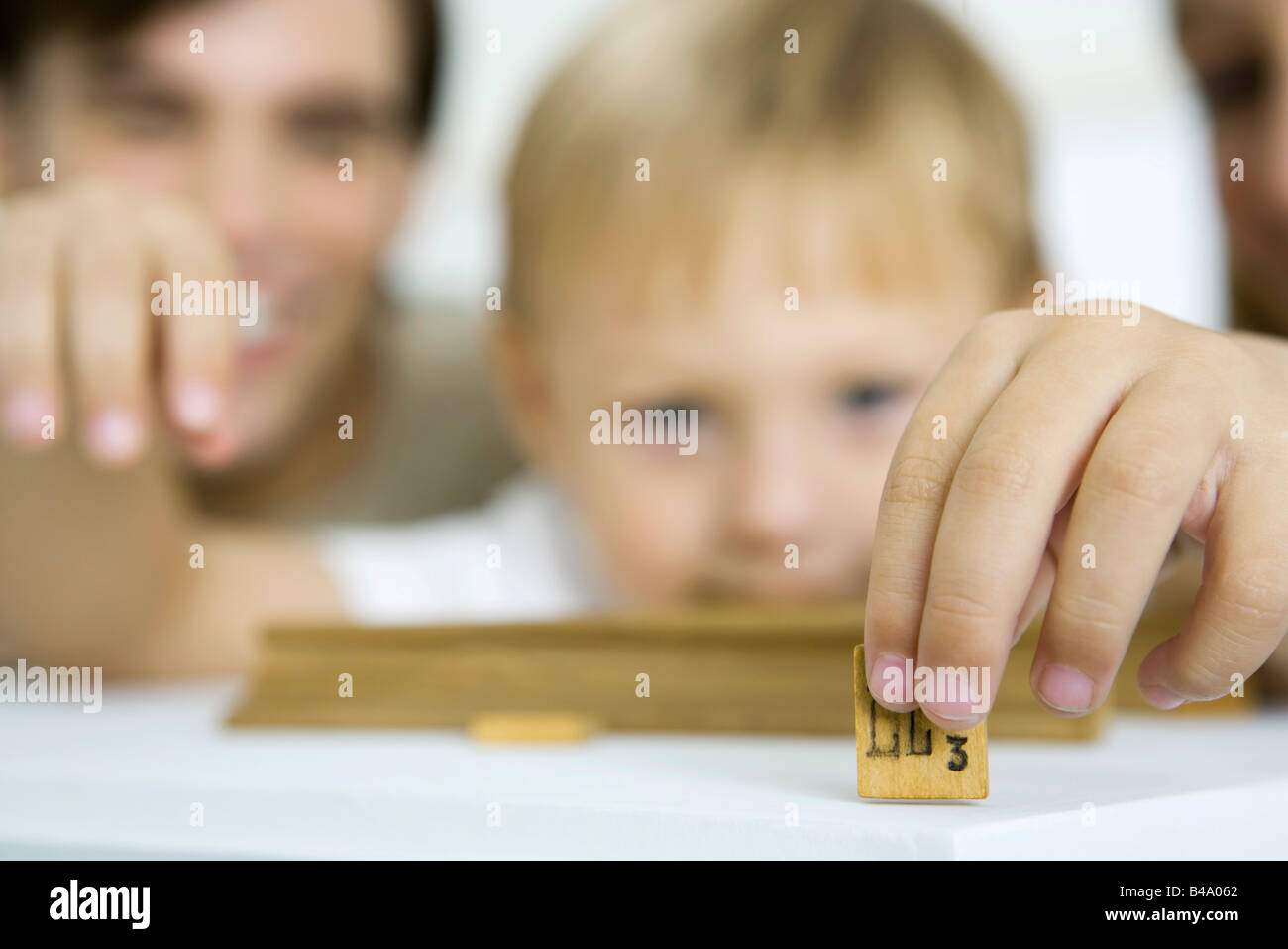 Little boy holding game piece, focus on foreground Stock Photo