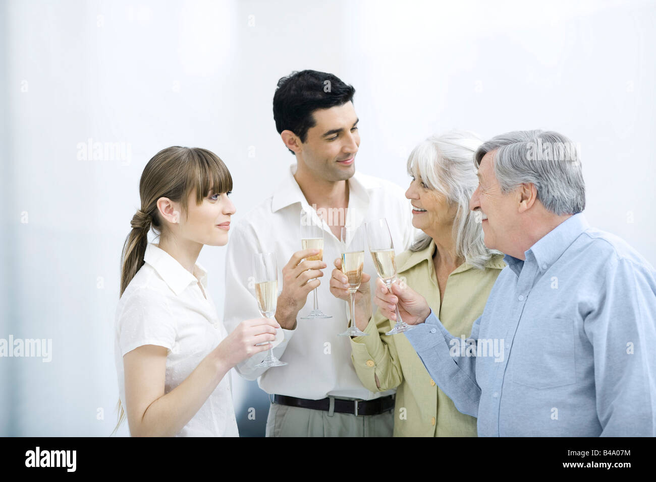 Couple standing with senior parents, all holding champagne flutes - Stock Image