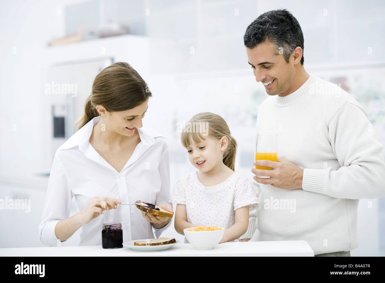 Parents and young daughter preparing breakfast in kitchen - Stock Image
