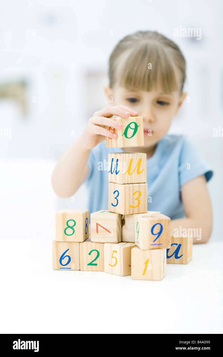Little girl stacking blocks, focus on foreground - Stock Image