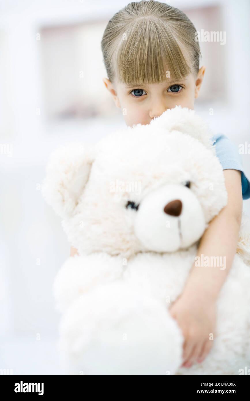 Little girl holding large teddy bear, portrait - Stock Image
