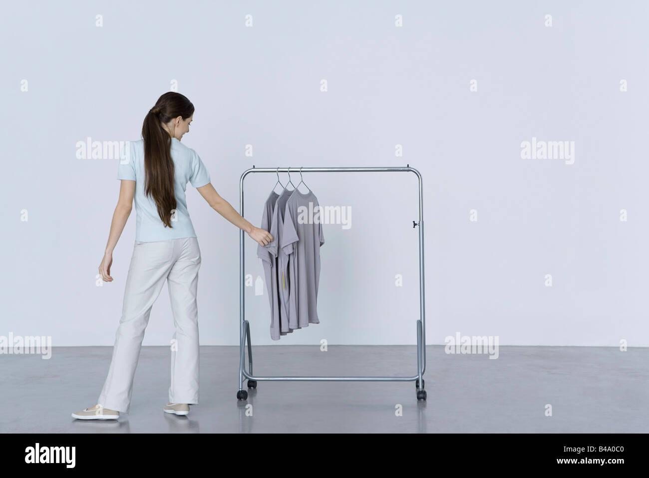 Woman looking at tee-shirts hanging on rack, rear view - Stock Image