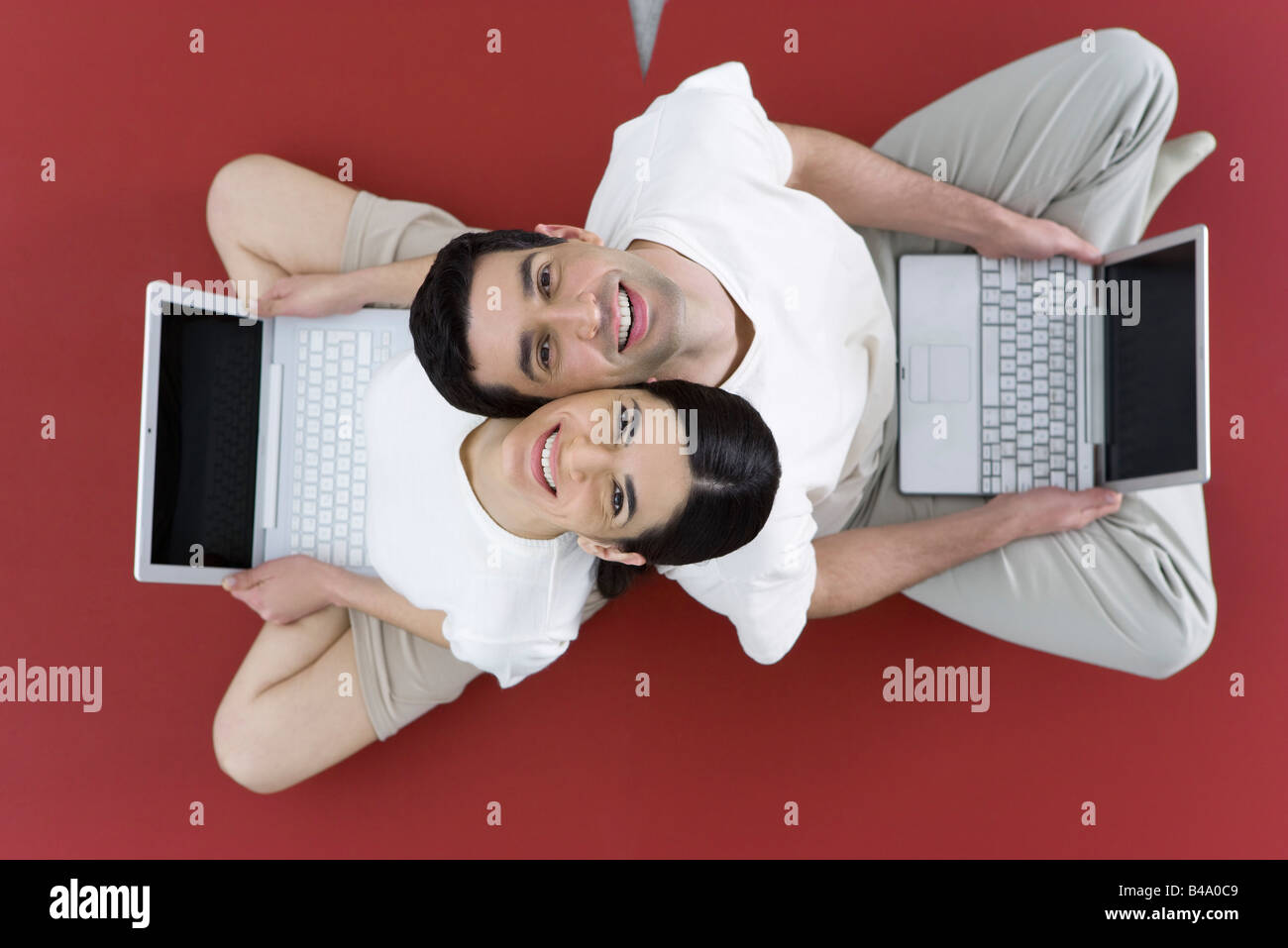 Couple sitting back to back on the ground, holding laptop computers, smiling up at camera - Stock Image