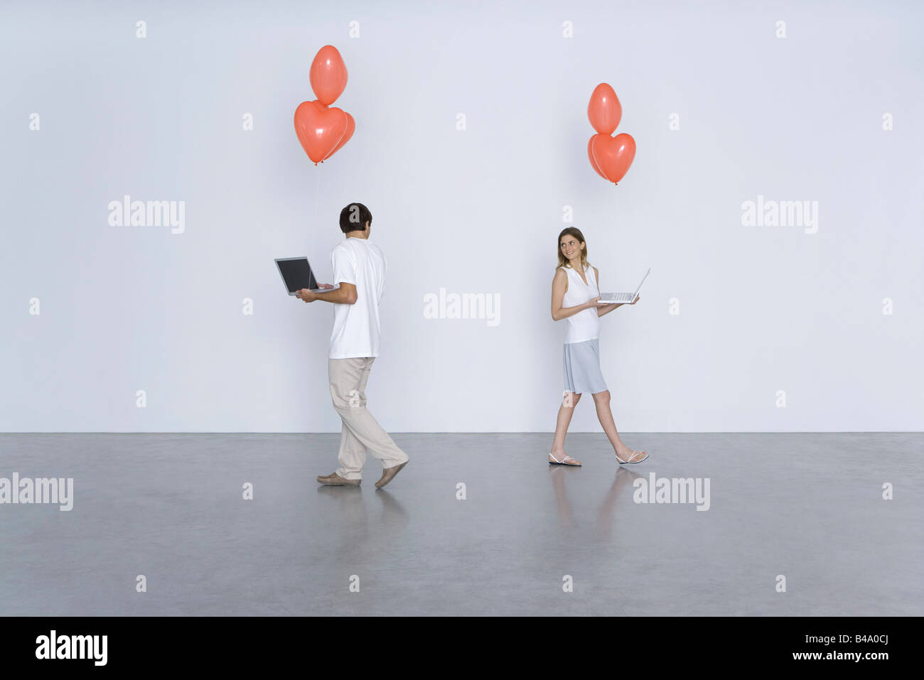 Man and woman carrying laptop computers and heart balloons, smiling over their shoulders at each other - Stock Image