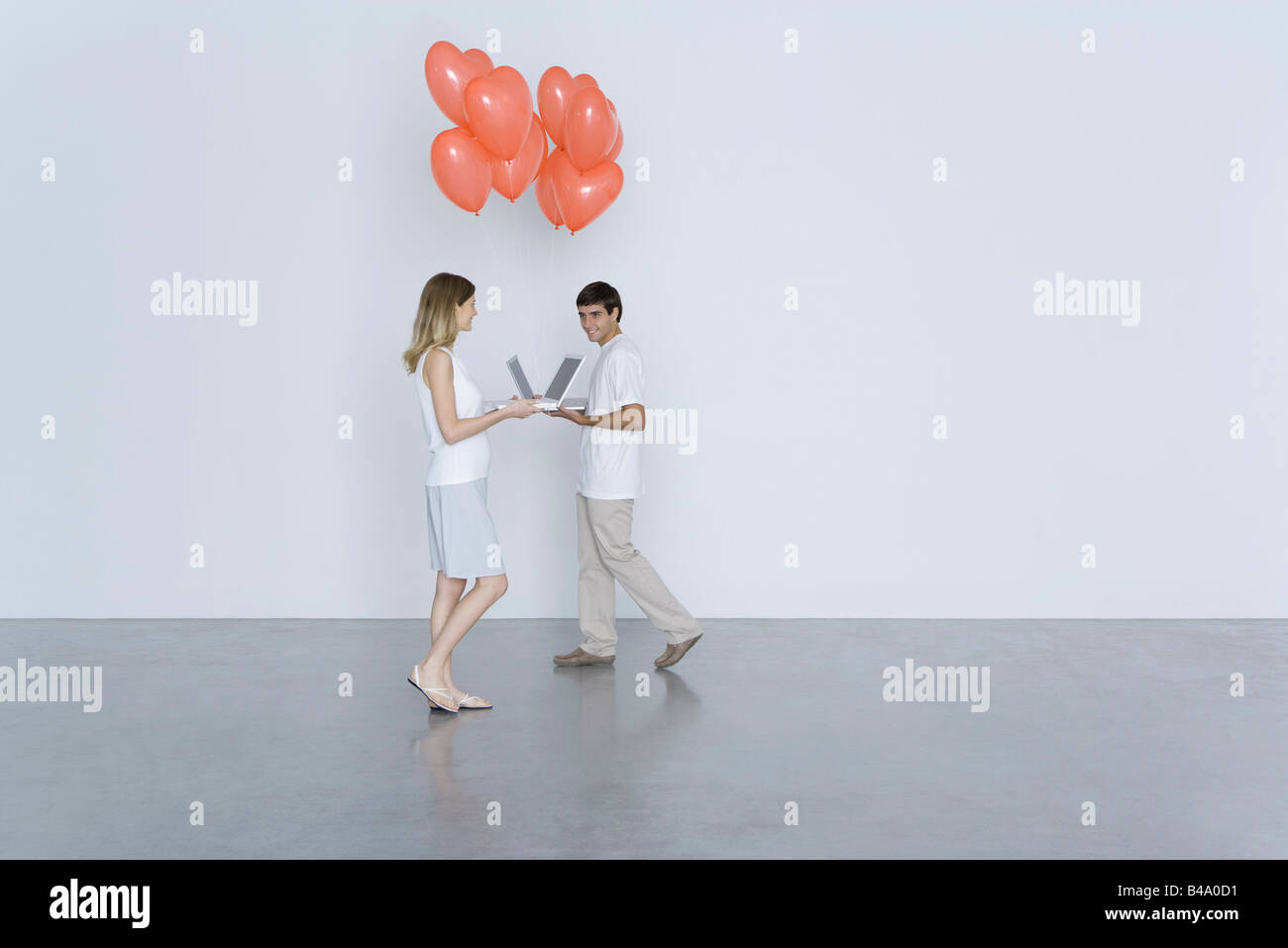 Man and woman walking toward each other with laptop computers and heart balloons, smiling - Stock Image