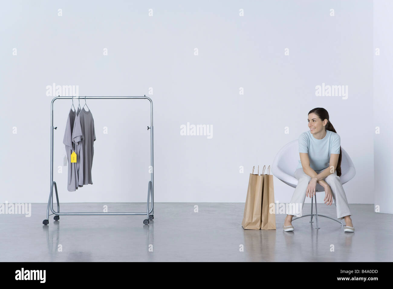 Woman sitting with shopping bags, looking at tee-shirts on nearby rack - Stock Image