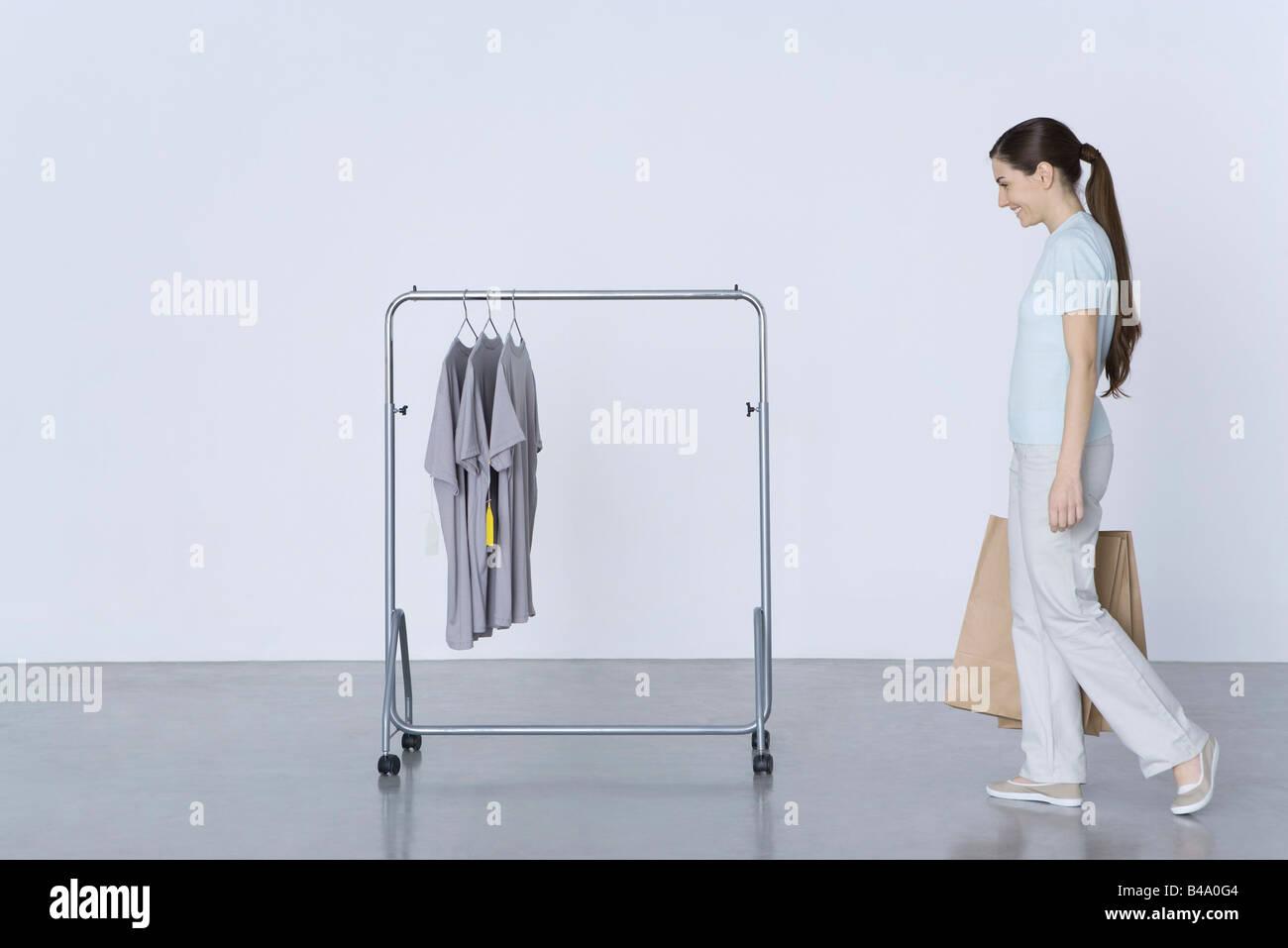 Woman walking toward rack of tee-shirts, carrying shopping bags - Stock Image