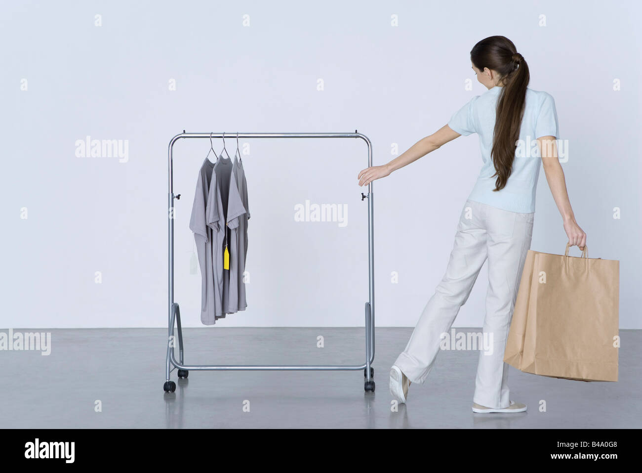 Woman carrying shopping bags and reaching toward tee-shirts on rack, rear view - Stock Image