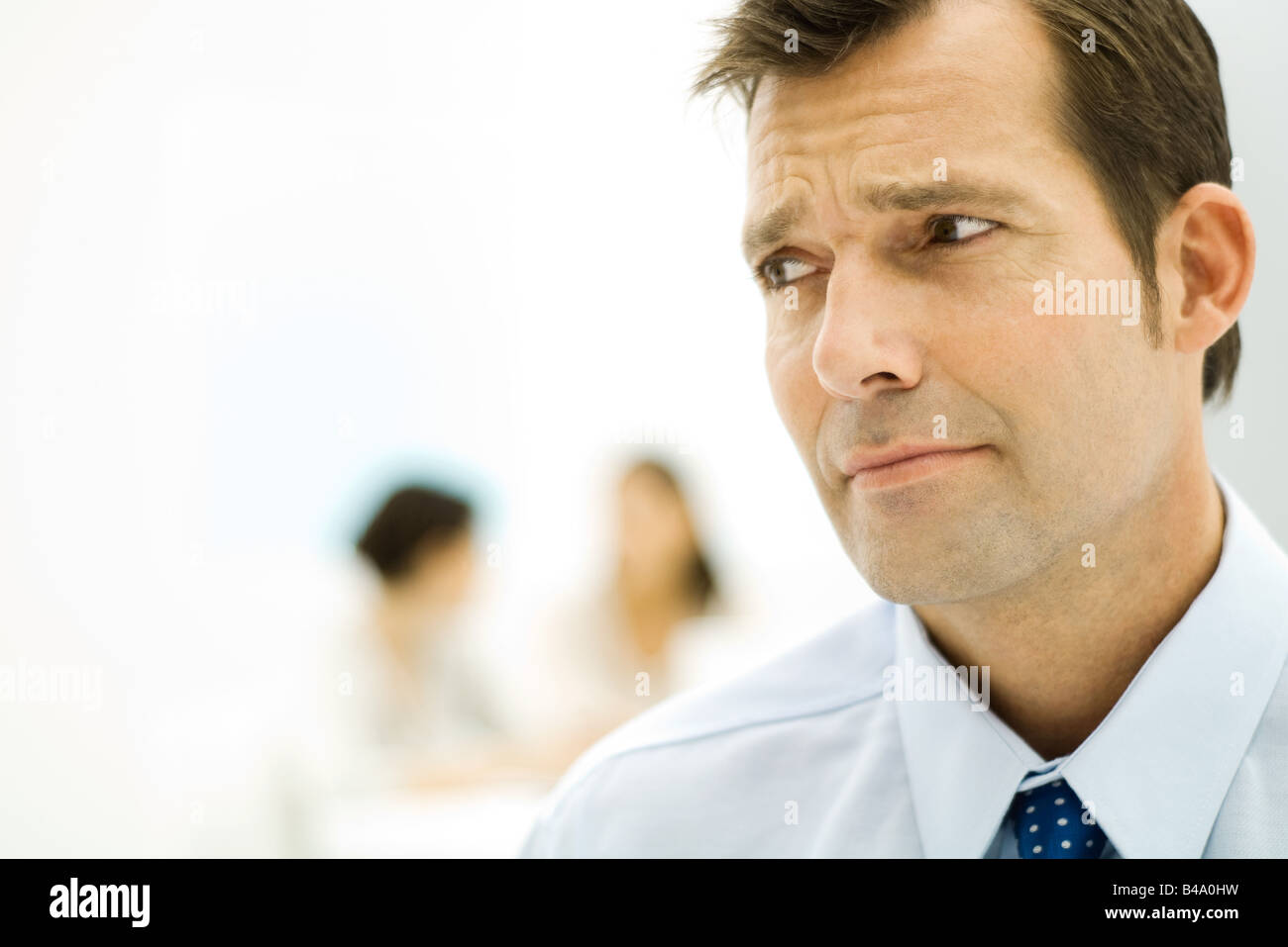 Businessman furrowing brow, looking out of frame, close-up - Stock Image