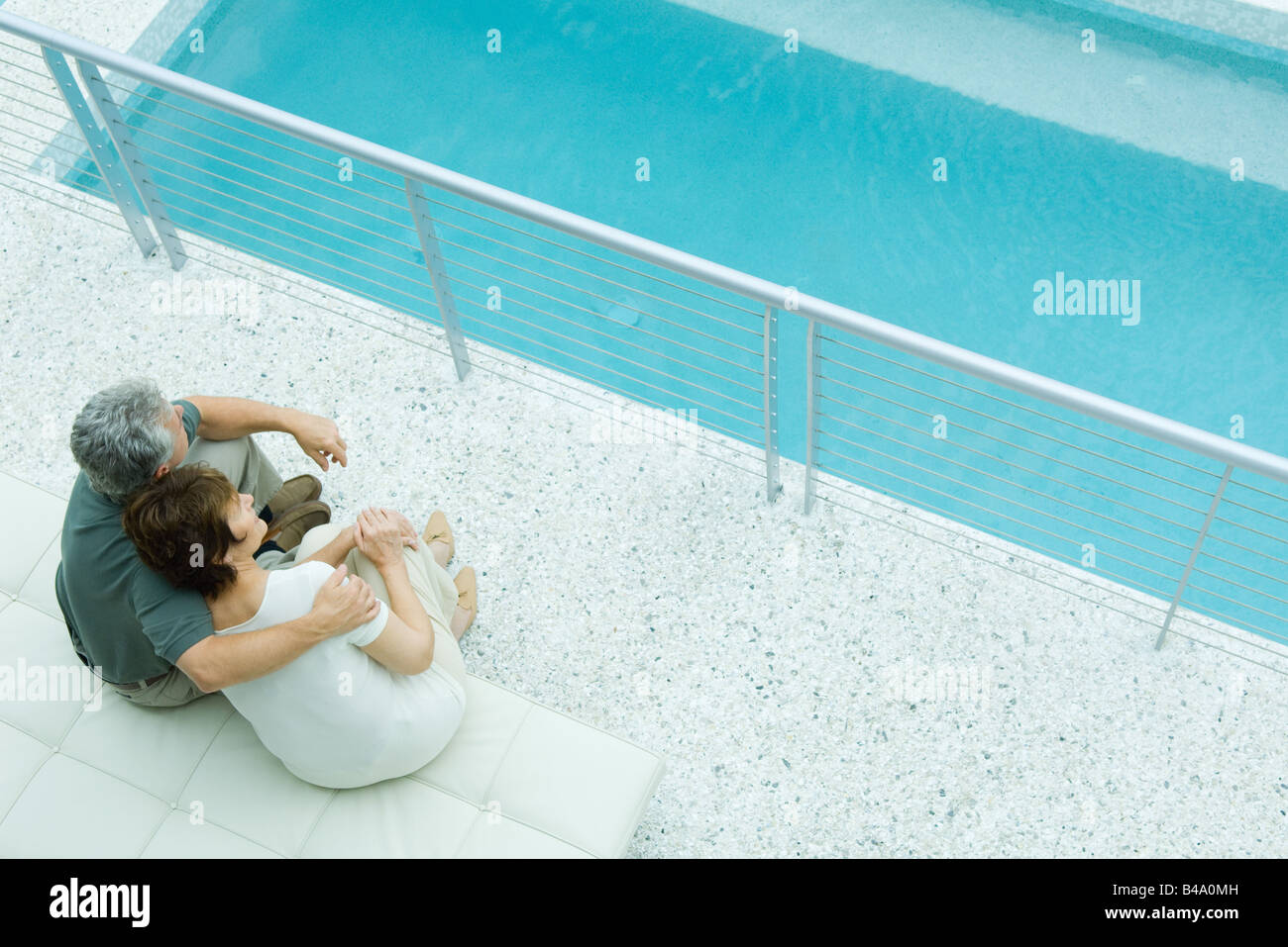 Husband and wife sitting by pool, his arm around her shoulder, her head on his - Stock Image