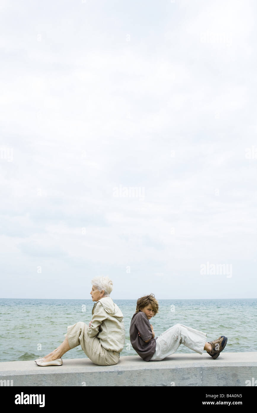 Senior woman with grandson, sitting back to back, not looking at each other - Stock Image