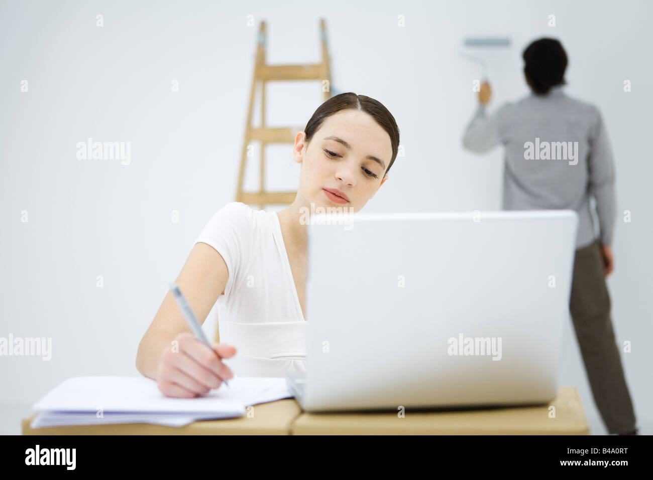 Young woman using laptop computer, man in background painting wall - Stock Image