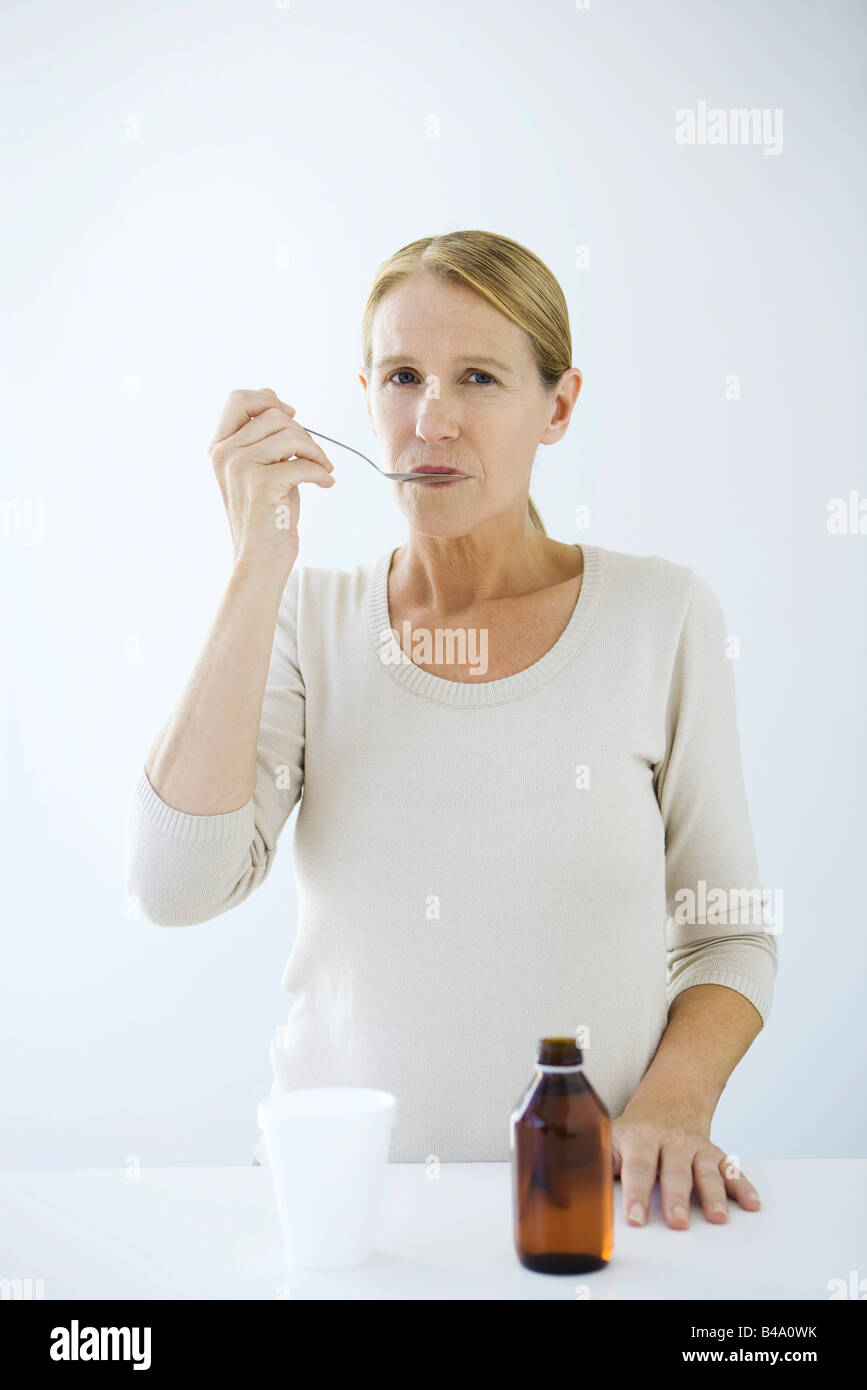 Woman taking spoonful of medicine, looking at camera - Stock Image
