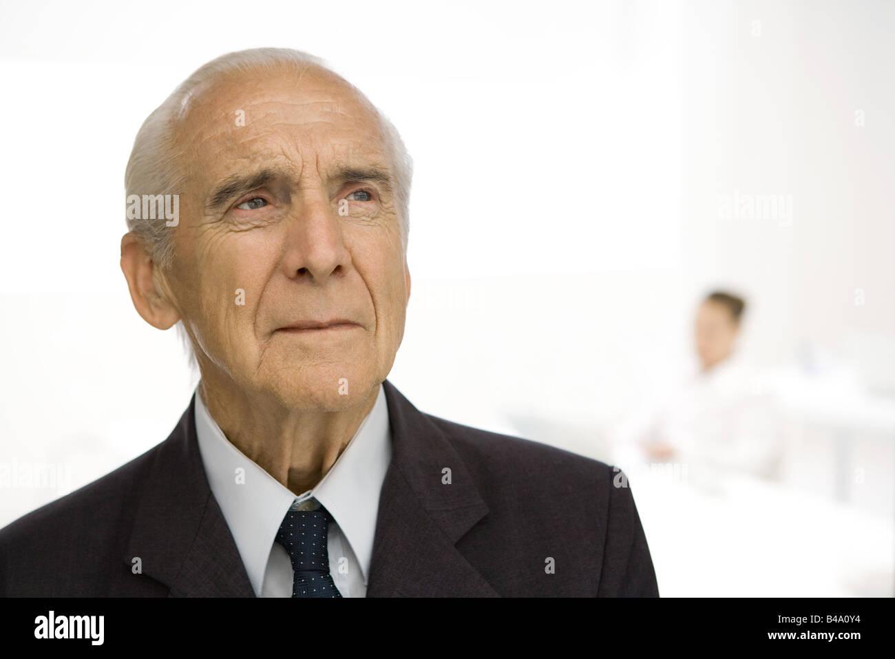 Senior man furrowing brow, looking away - Stock Image