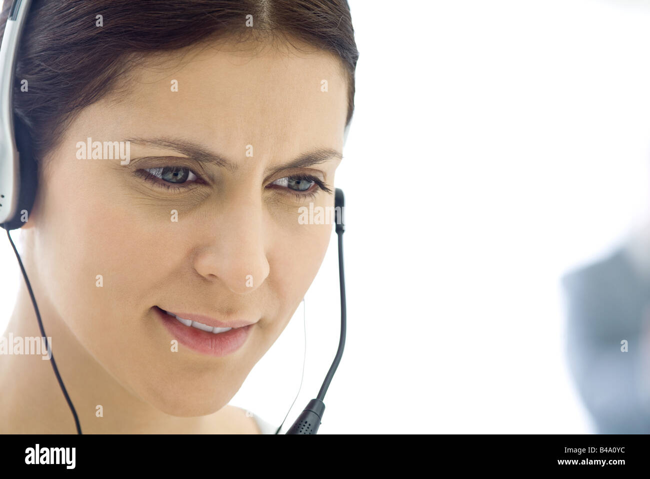 Woman wearing headset, looking down, close-up - Stock Image