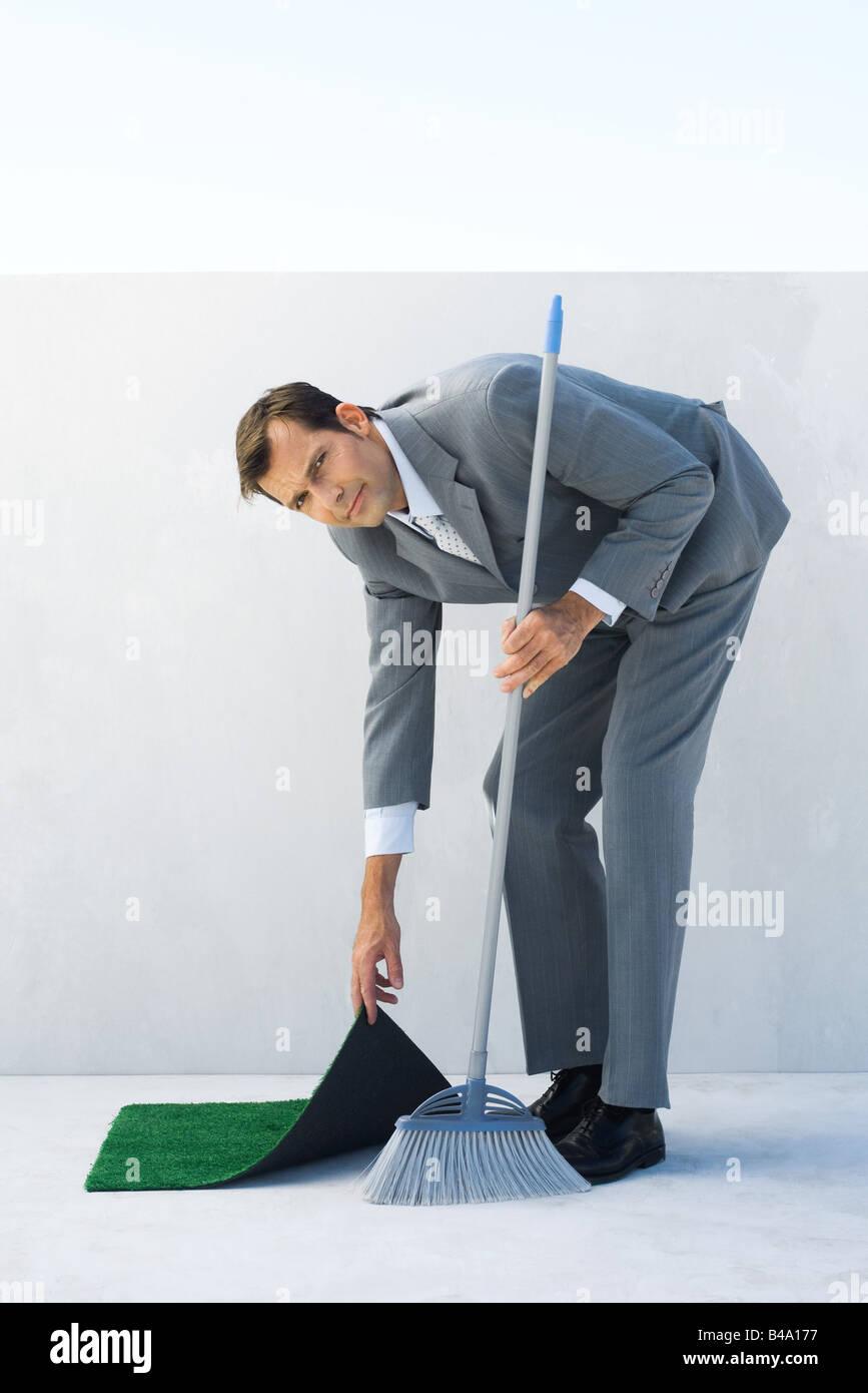Businessman sweeping, lifting corner of rug, looking at camera - Stock Image
