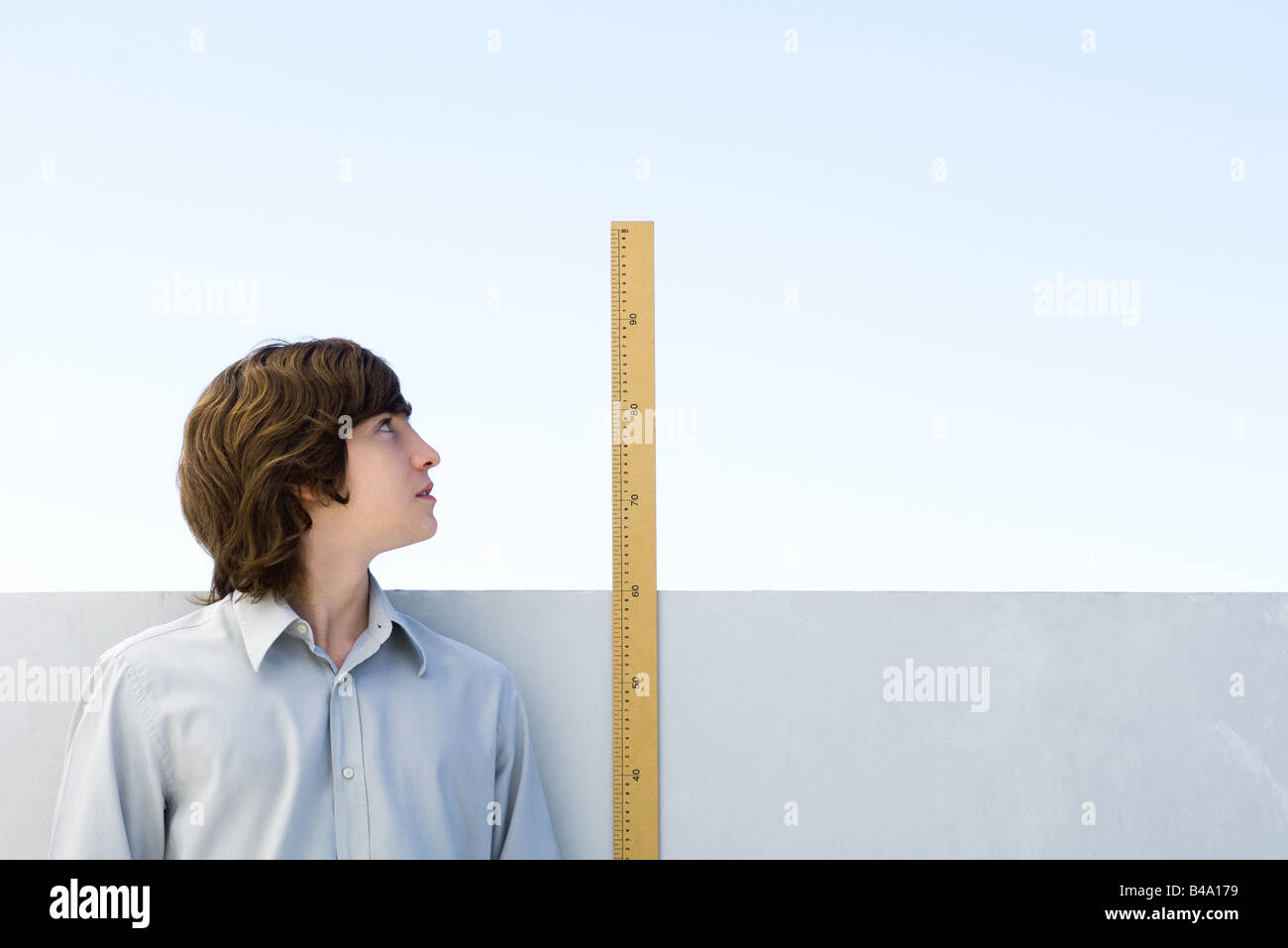 Young man measuring his height with ruler - Stock Image