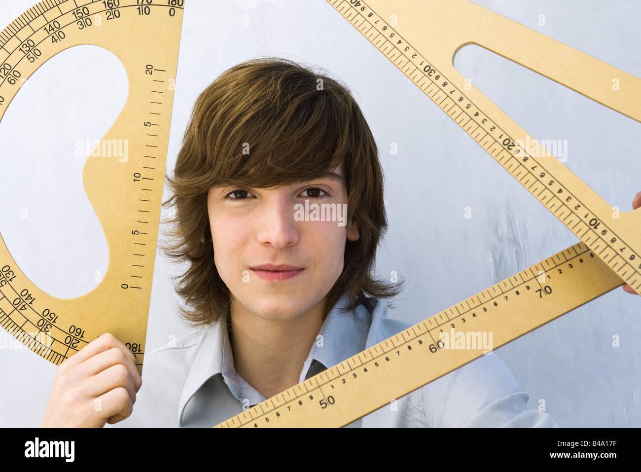 Young man holding various measuring instruments, smiling at camera - Stock Image