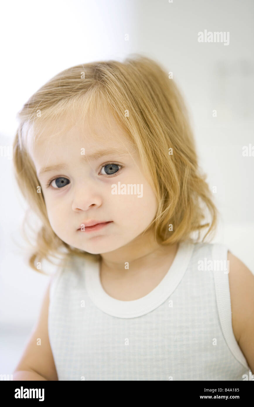 Toddler girl looking at camera, portrait - Stock Image
