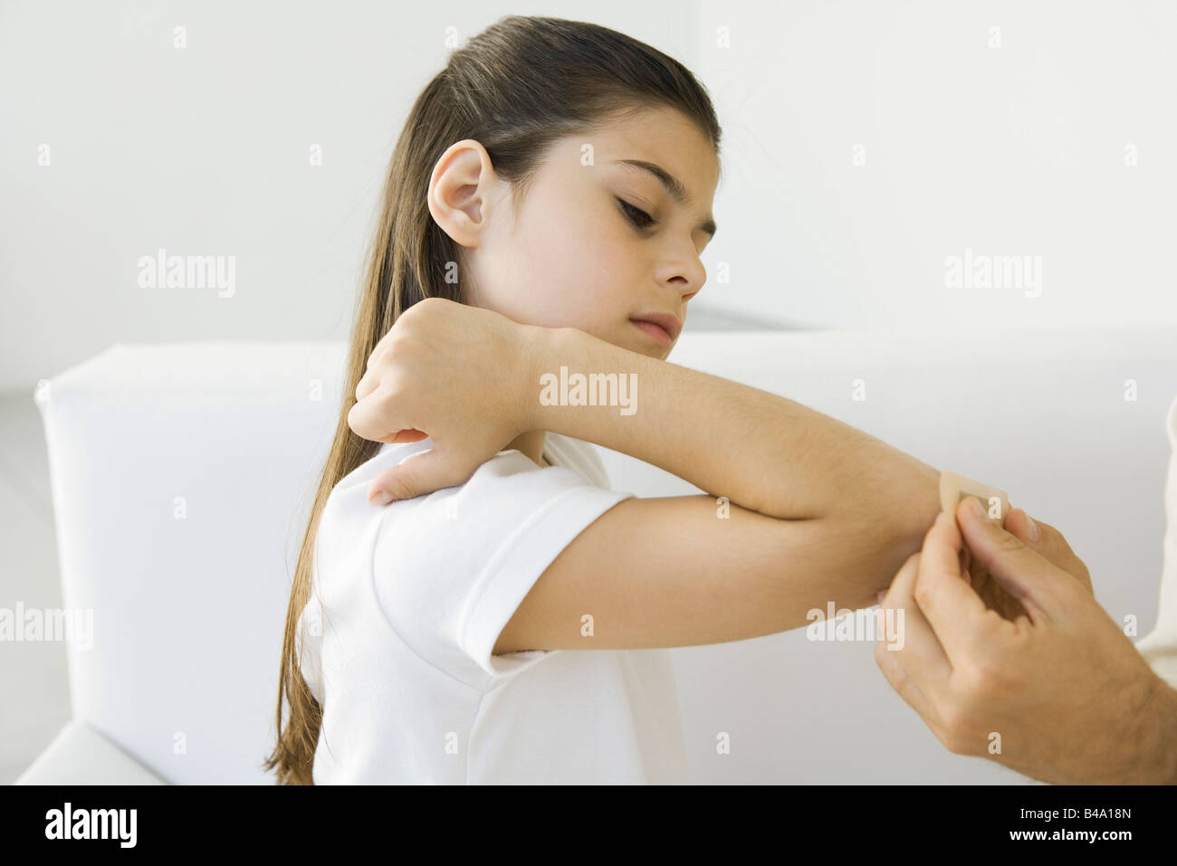 Man putting adhesive bandage on girl's elbow, cropped view Stock Photo