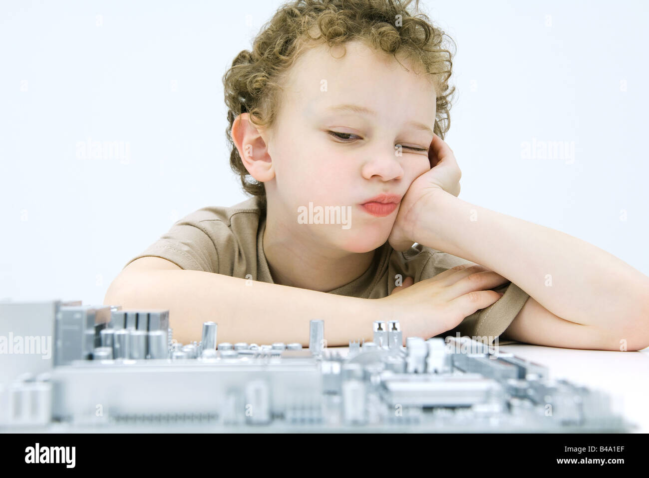 Little boy leaning on elbow, contemplating computer motherboard - Stock Image