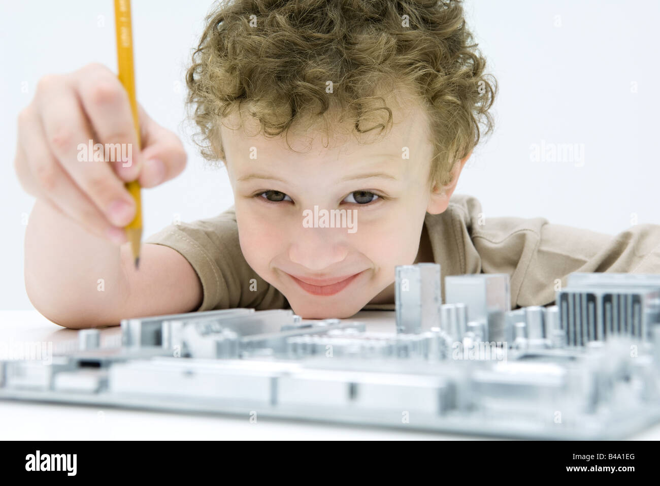 Little boy holding pencil over computer motherboard, smiling at camera - Stock Image