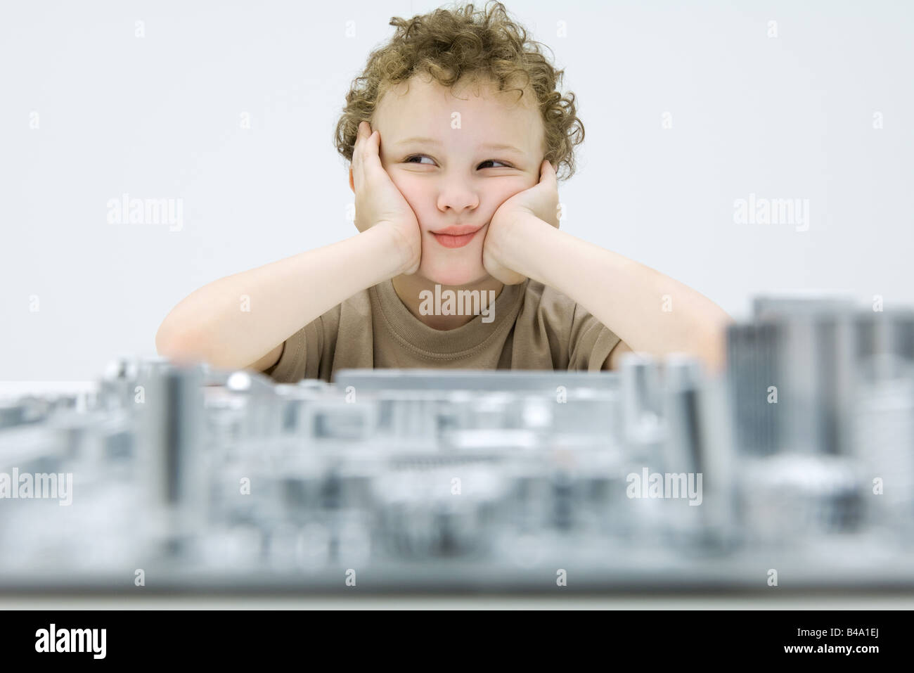 Little boy sitting with computer motherboard, holding head, looking away - Stock Image