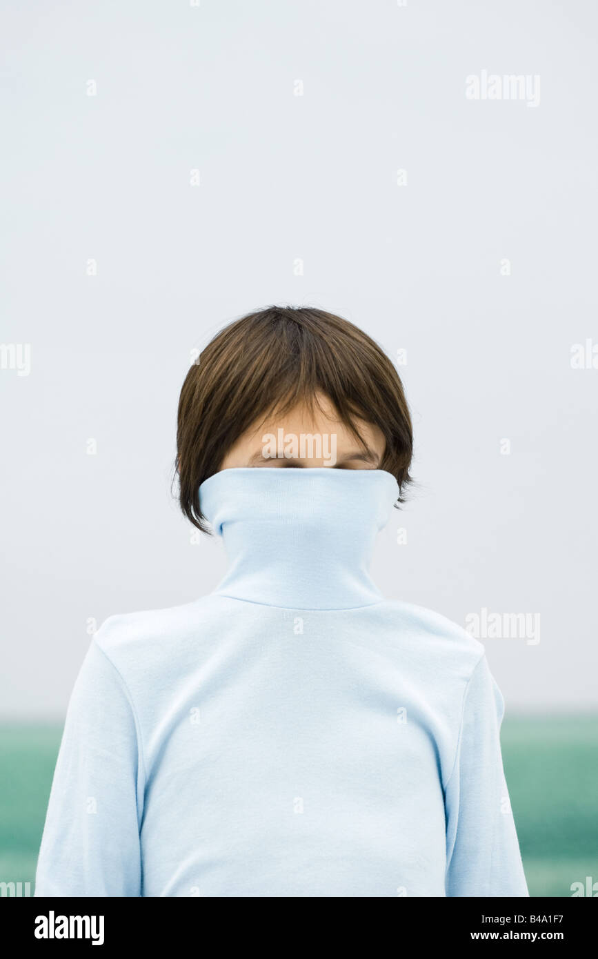 Boy with turtleneck pulled over face, portrait - Stock Image
