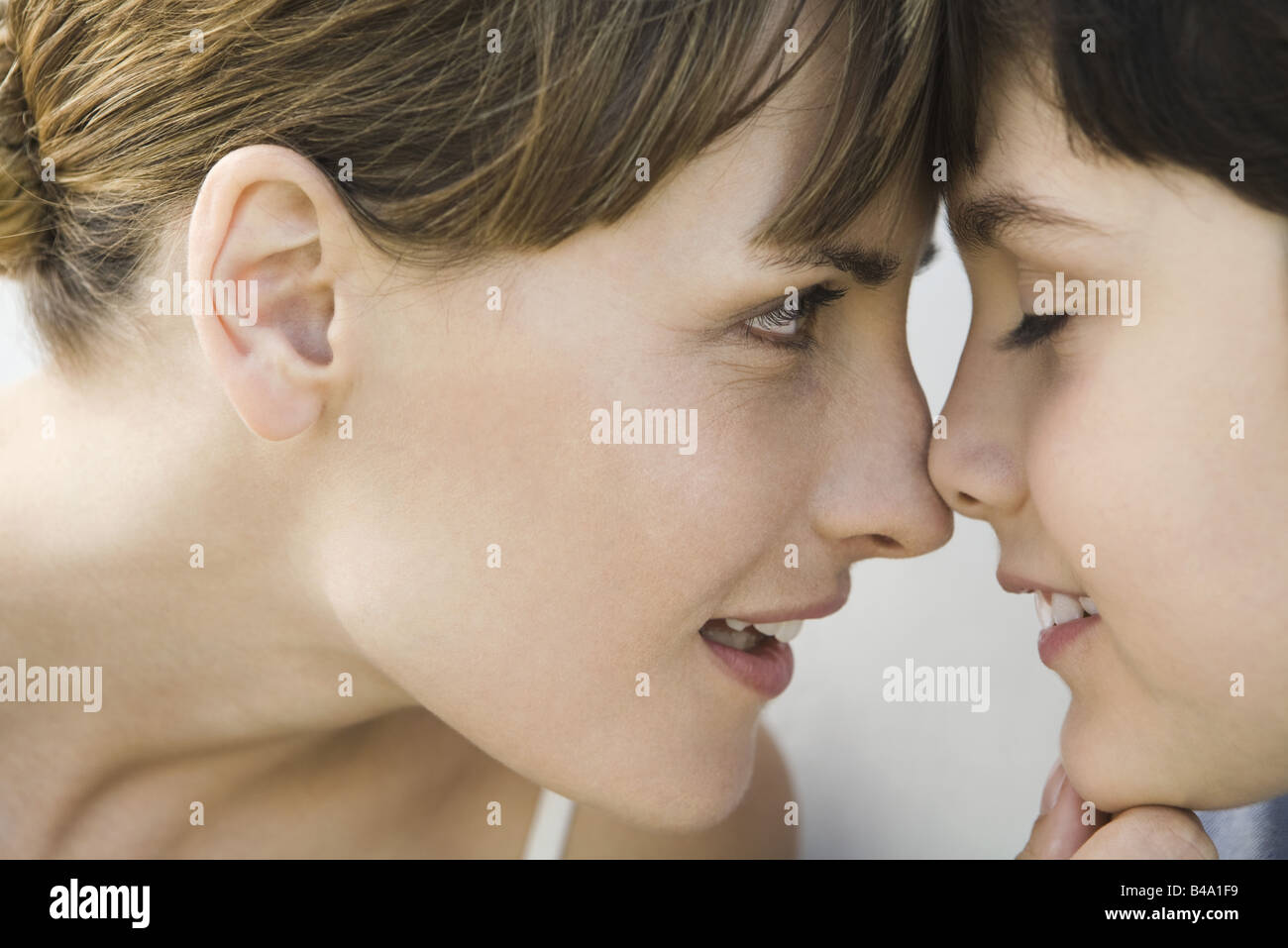 Mother and son touching noses, boy's eyes closed, side view - Stock Image