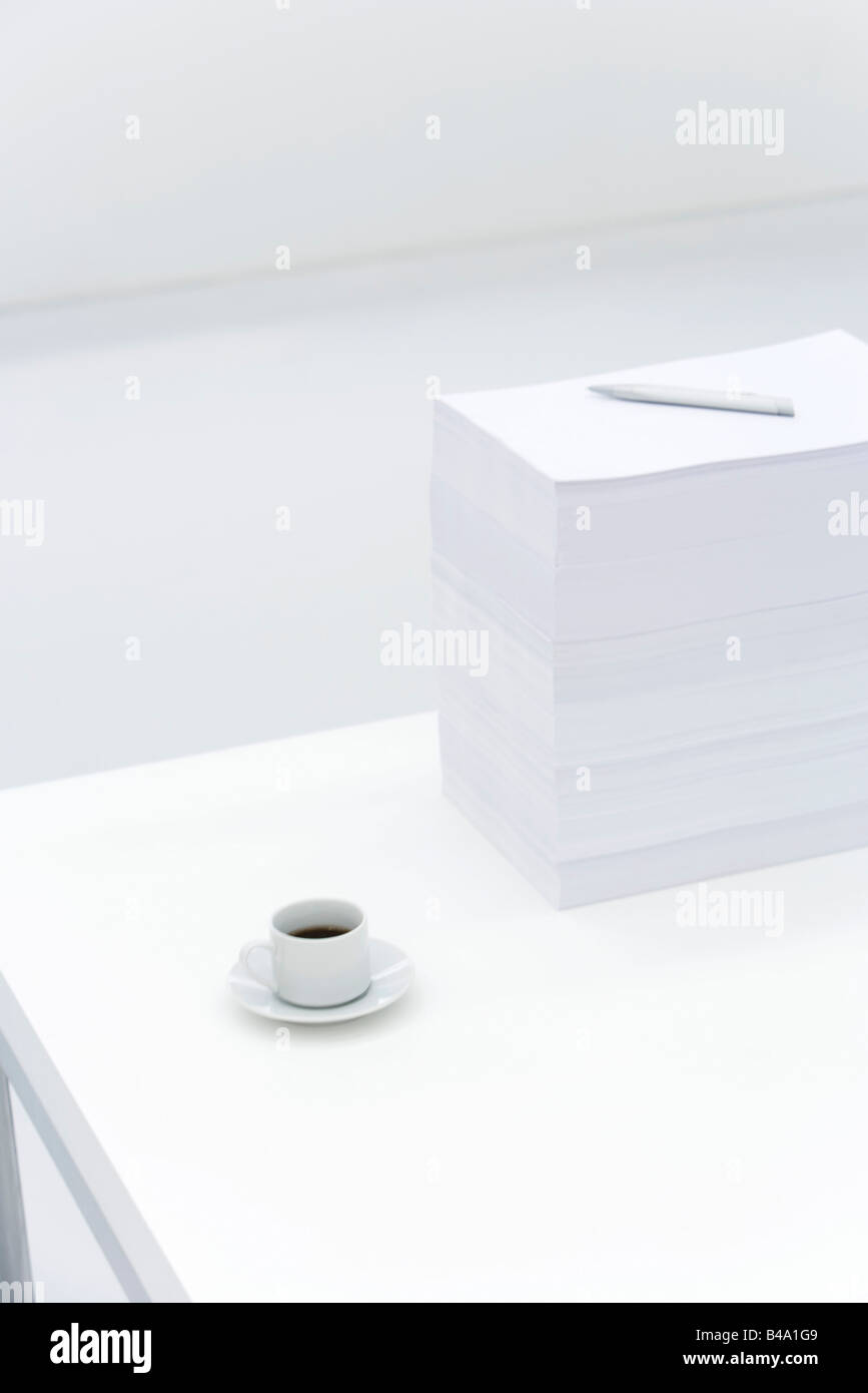 Coffee cup and large stack of documents on desk - Stock Image