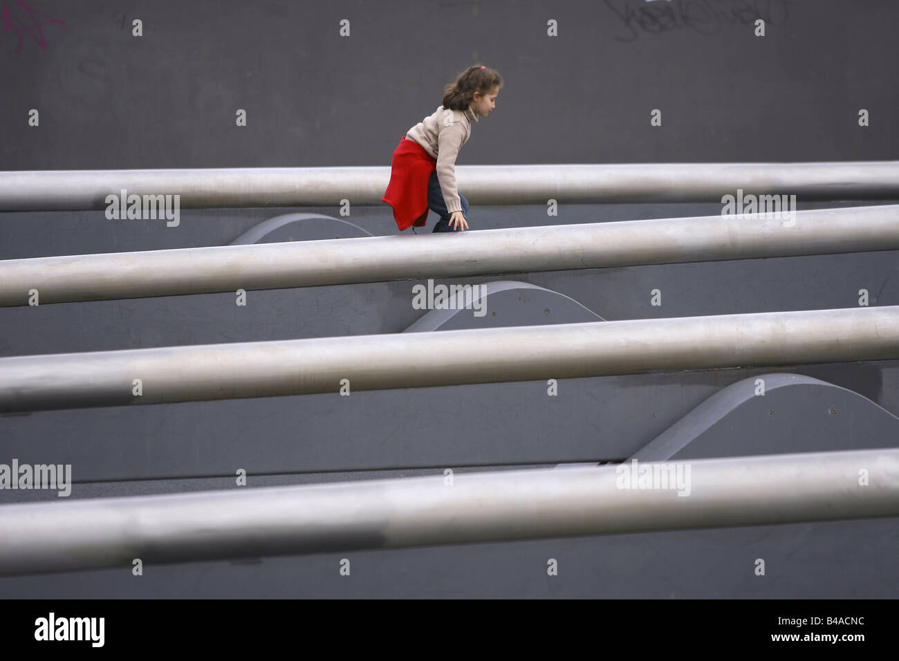 Young girl on Europes longest seesaw in Tilla-Durieux-Park, Berlin, Germany - Stock Image