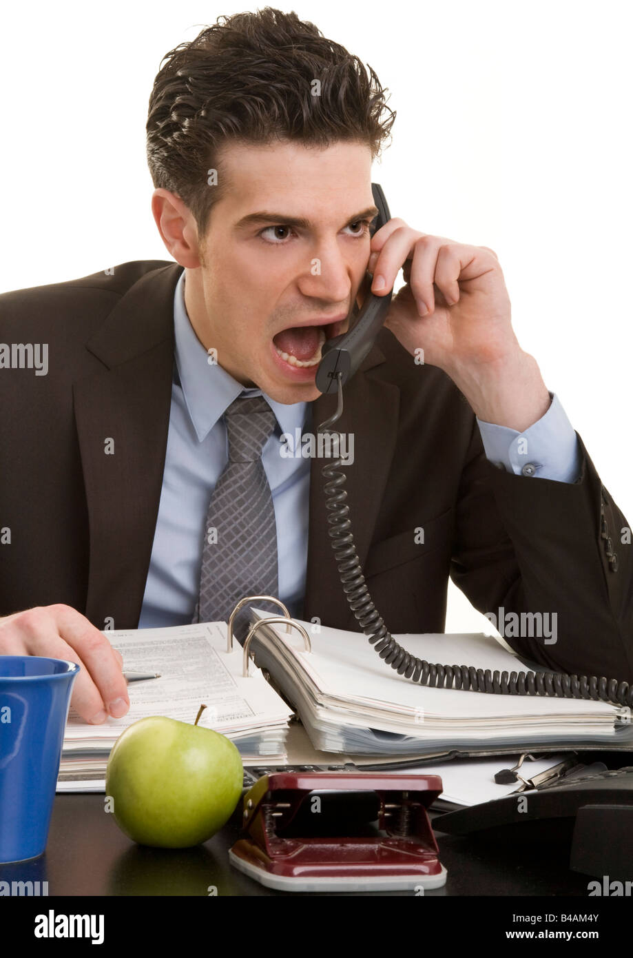 young manager crying into the telephone - Stock Image