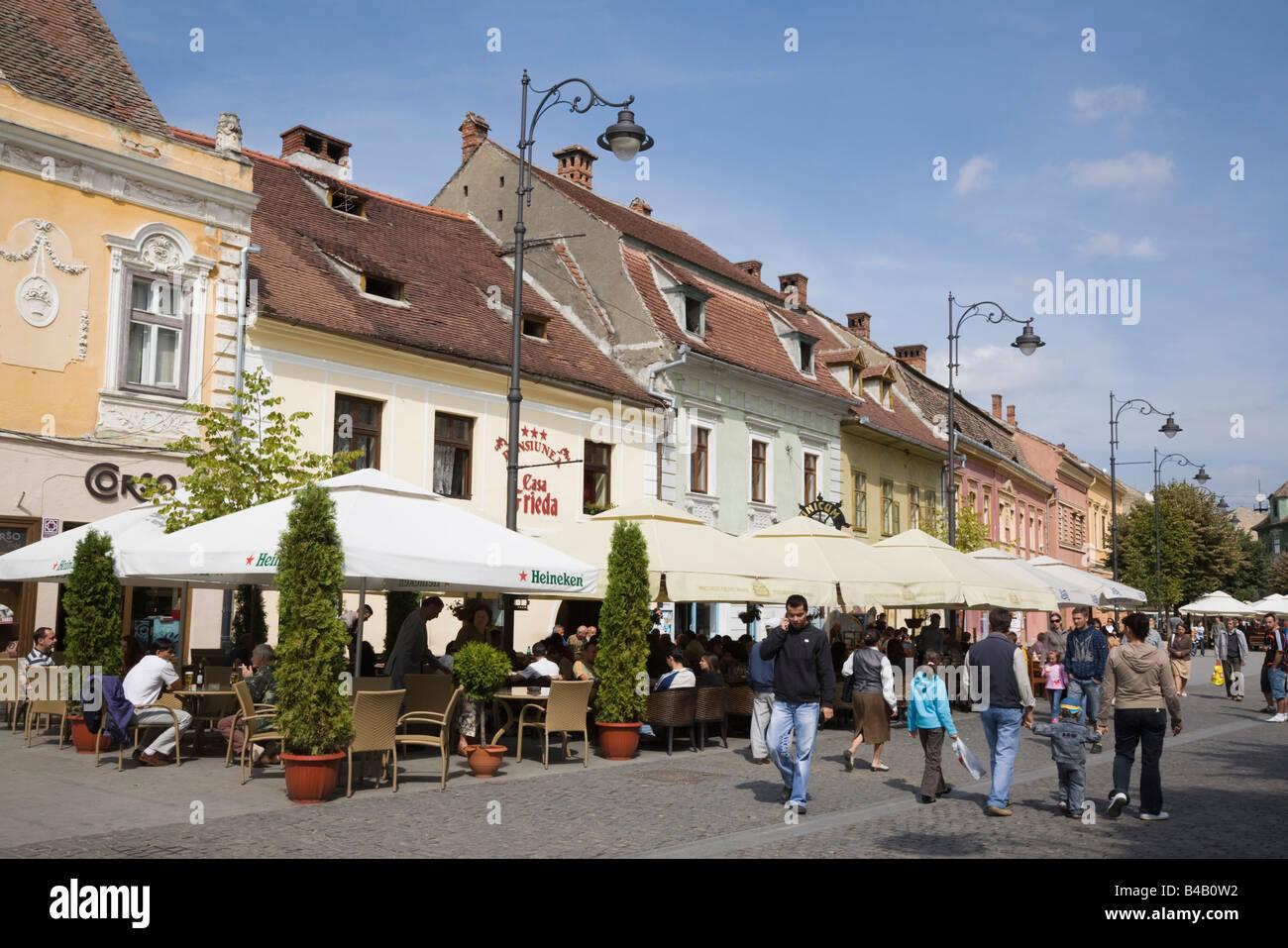 Sibiu Transylvania Romania Street cafes with umbrellas and outdoor seating on pedestrian precinct in historic city - Stock Image