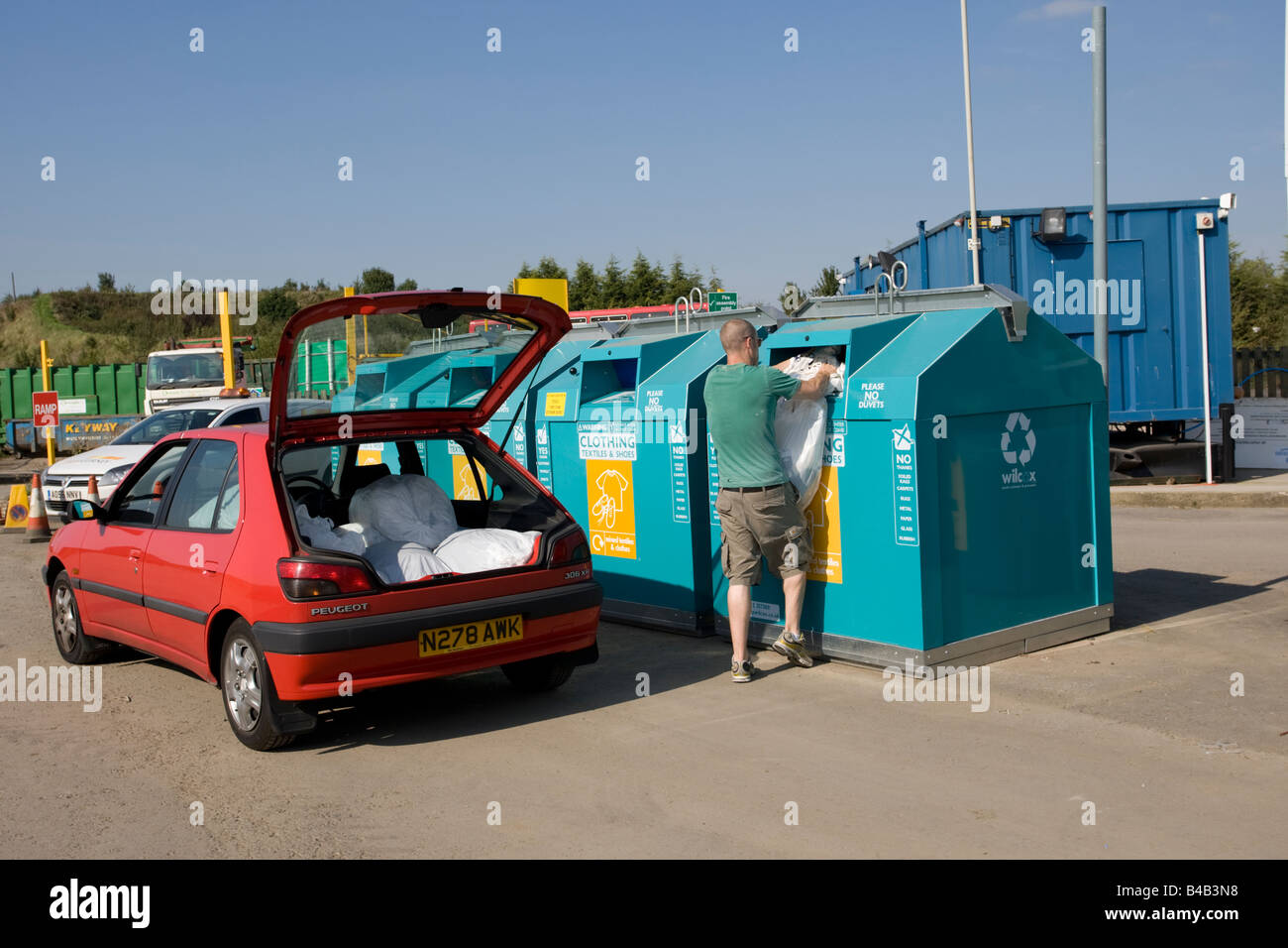 Man recycling clothes domestic waste site Wingmoor Farm Stoke Orchard Cheltenham UK - Stock Image