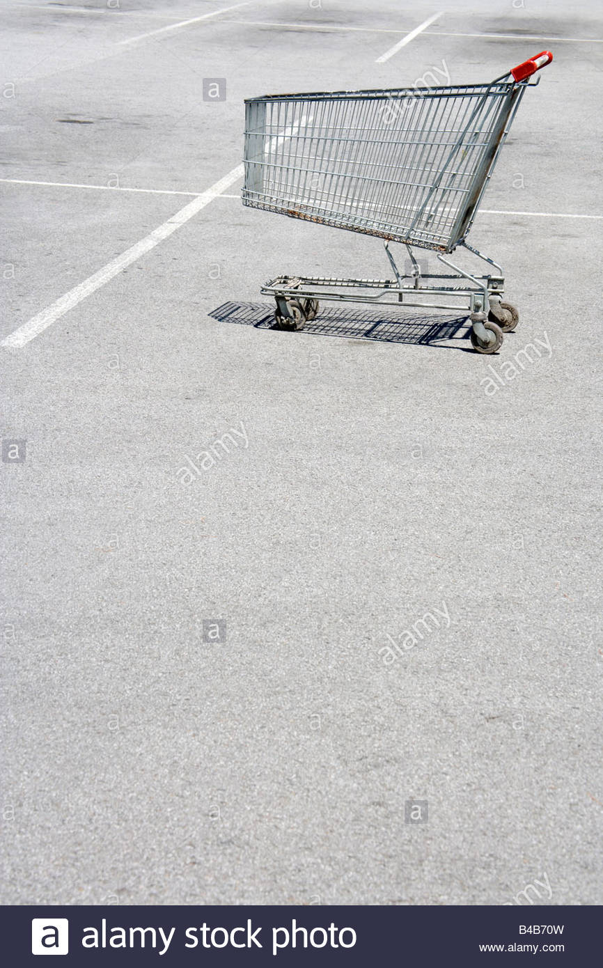 empty shopping cart parked in a car parking spot - Stock Image