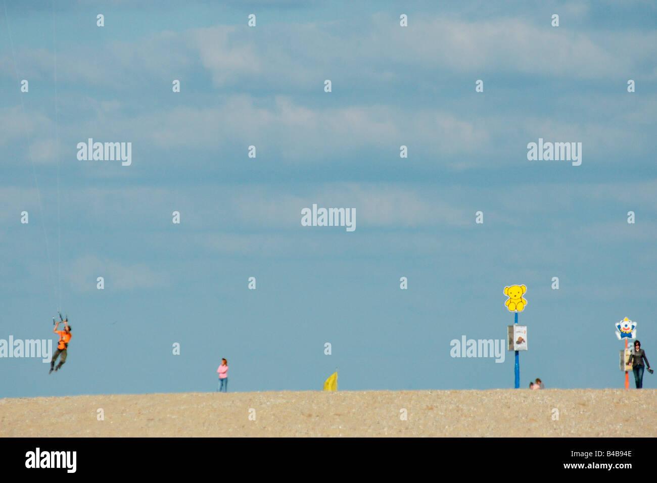 Woman walking sand beach with signs man flying powerkite in high wind at summer under blue sky Hoek van Holland - Stock Image