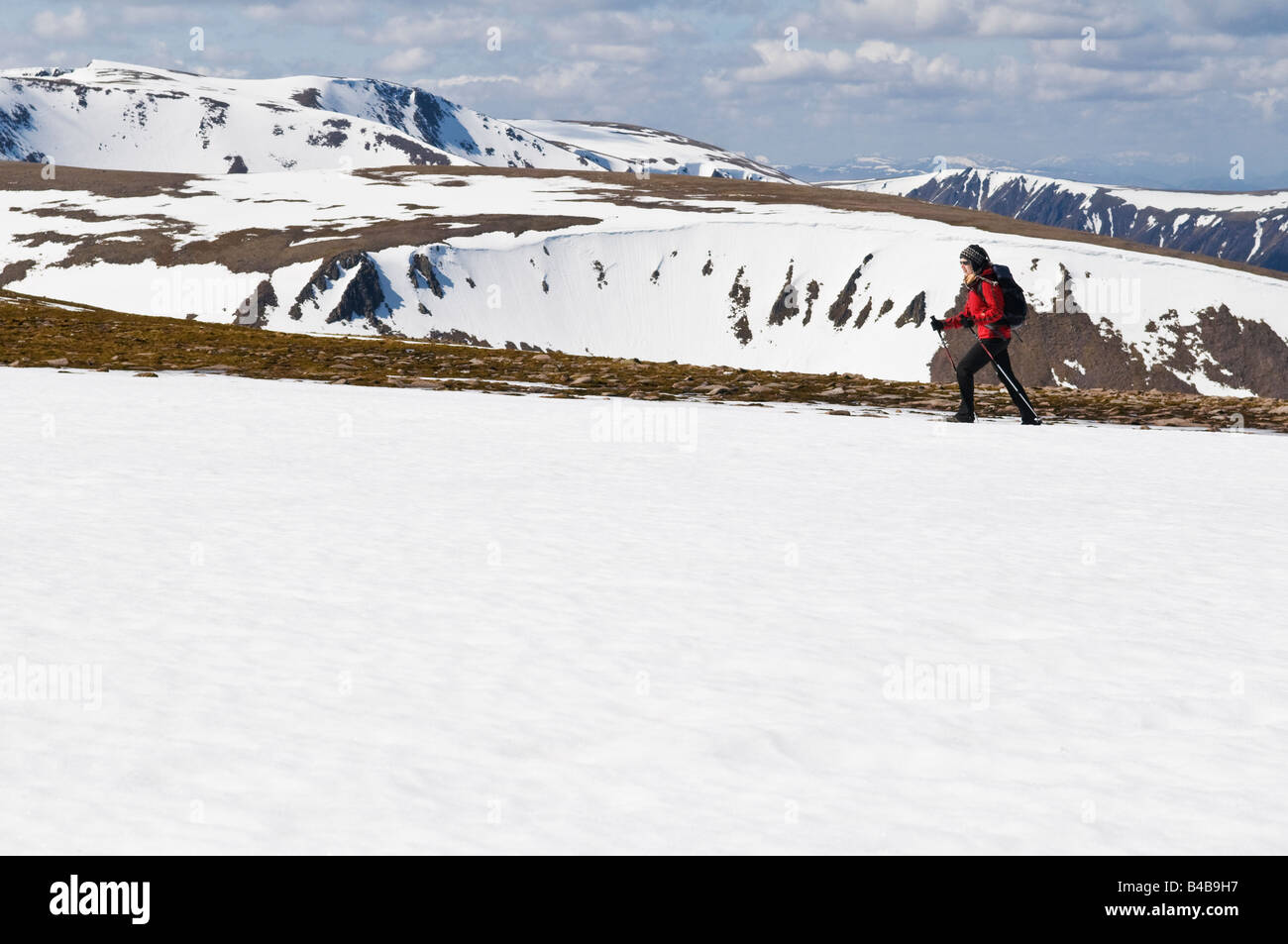 Female hiker in red jacket crosses snowfield near summit of Cairn Lochan in the Cairngorm mountains, Scotland - Stock Image