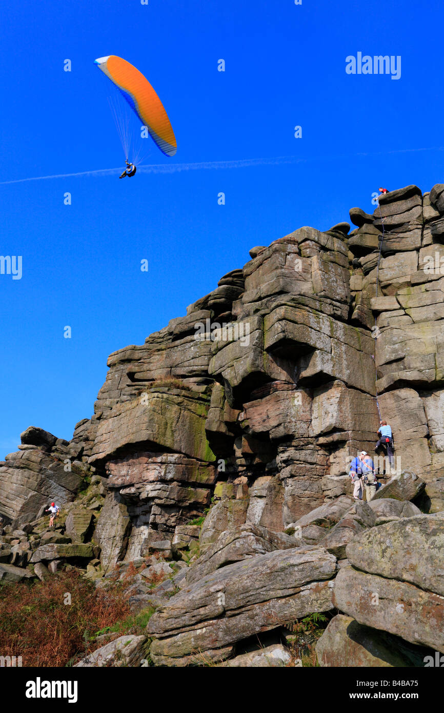 Paraglider and rock climbers on Stanage Edge Hathersage Derbyshire England UK - Stock Image