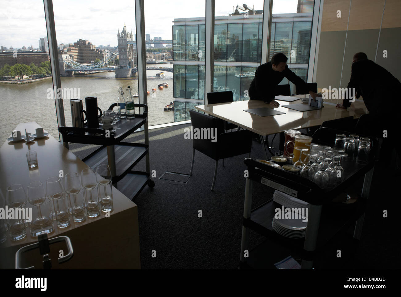 Top floor restaurant waiters prepare for executive lunch meetings in an auditing company's European headquarters - Stock Image